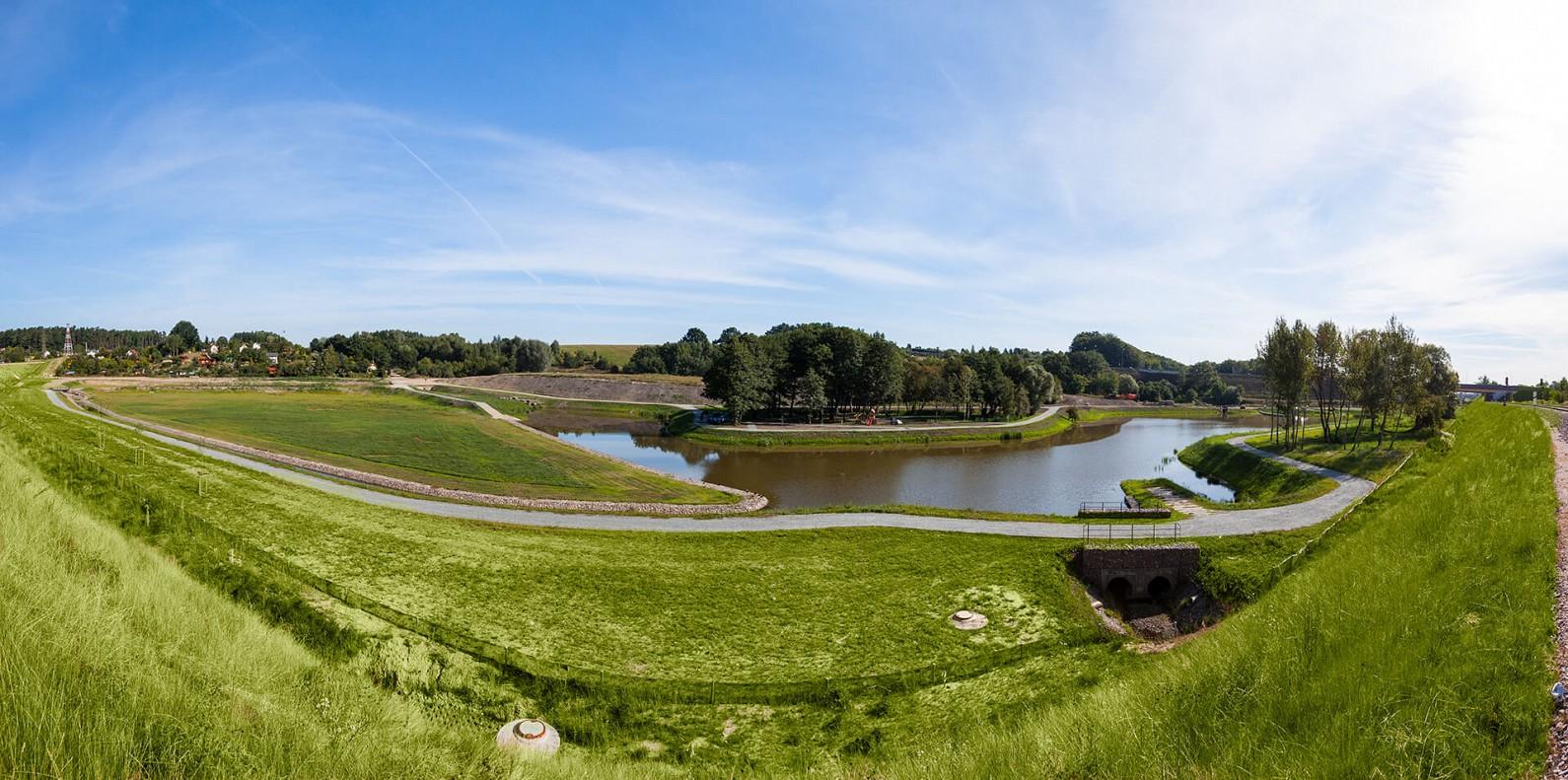 Gdańsk na podium. Na zdjęciu widoczny zbiornik wodny z okalającą go zielenią. Na drugim planie szpaler drzew.